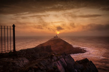 The Sun Emerging To Light Up The Clouds At Daybreak Over Mumbles Lighthouse In Swansea, South Wales, UK
