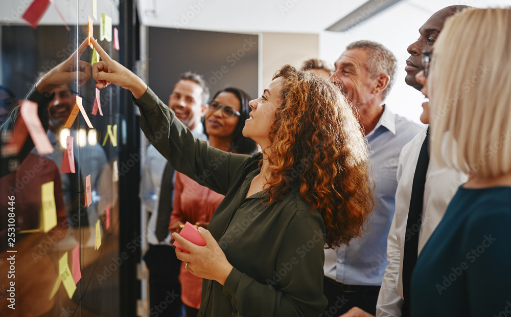 Fototapeta Diverse businesspeople brainstorming with sticky notes in an off