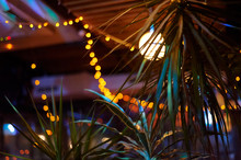 Tropical Bar Athmocphere Background With Yellow Garland Bokeh. Vacation Night Life Concept