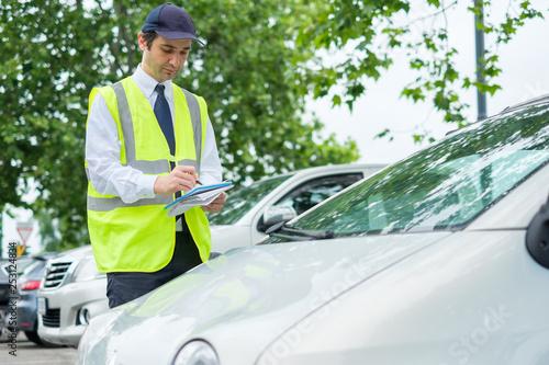 Obraz Parking officer writing a ticket for a parking violation - fototapety do salonu