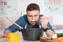 Concentrated Young Man Preparing Food At Home