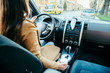 woman driving car and drinking coffee. phone navigation