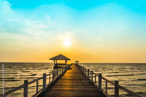Foto auf AluDibond Licht blau perspective view of wooden bridge extending into the sea on the beach