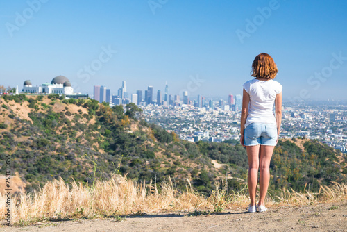 Fototapeta Young woman is looking at the city of Los Angeles, California, USA from Griffith Park