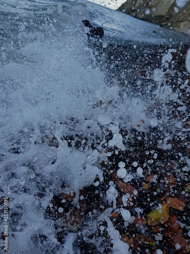 Fotografija  Welle schlägt auf Steinstrand auf