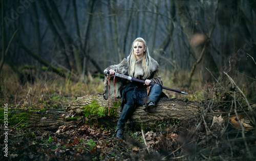 Mad furious viking woman warrior with a sword in her hands, in the woods Wallpaper Mural