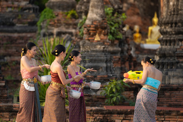 Songkran festival in Thailand. Happy Thai girls in Thailand cultural costume play water in the Thai new year festival called Songkran day.