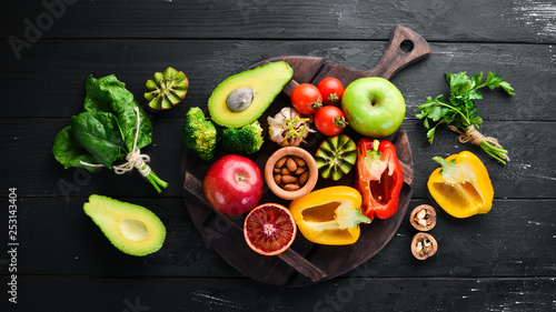 La pose en embrasure Cuisine Fruits and vegetables containing fiber: Avocados, kiwi, apple, tomatoes, spinach, paprika, orange, lemon. Top view. Free space for your text. On a black background.