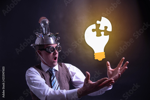 Photographie Funny nerd or geek with aluminium hat looking to light bulb having an idea