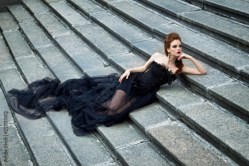 Fototapety, obrazy: Art work Gothic fashion: a beautiful young girl in black dress and headwear sitting near castle. Toned and noise added.