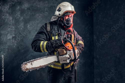 Fotografie, Obraz  Firefighter in safety helmet and oxygen mask holding a chainsaw
