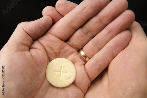 Fotografia Cupped hands of a man holding a wafer of bread The Body of Christ when receiving