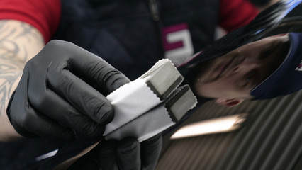 A professional worker guy (Male) applies ceramics (special liquid) to the car using an applicator (sponge) in black gloves and in a protective robe. Concept of: Auto service, Deteyling.