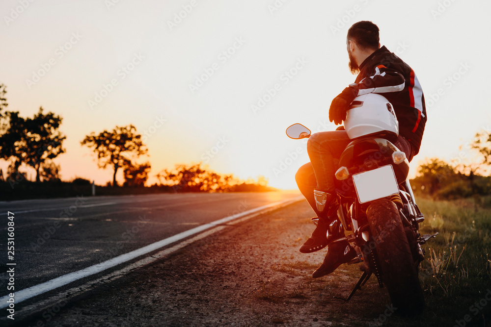 Fototapeta Confident attractive european biker sitting on his bike and looking at the sunset contemplating while resting in his traveling on the bike.