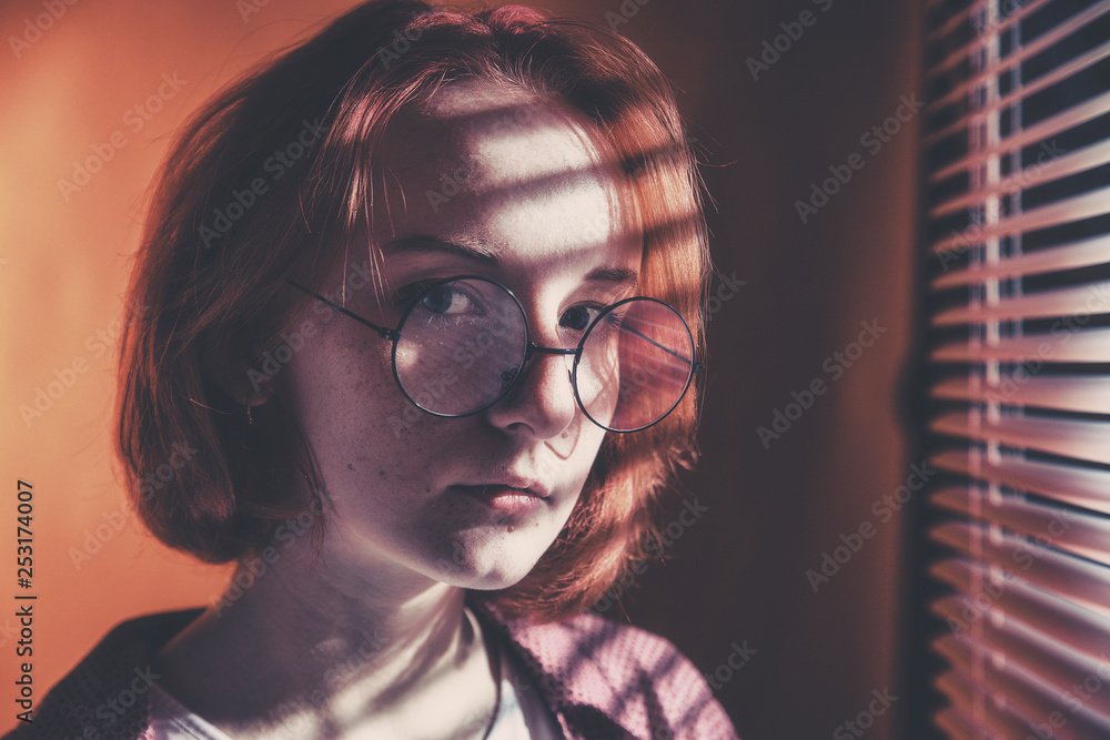 Fototapeta Red-haired girl with glasses in a plaid shirt and a white t-shirt is sad at the window with blinds - obraz na płótnie