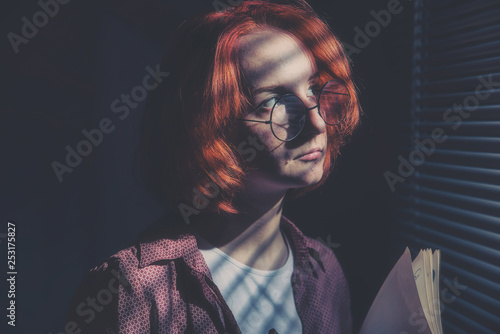 Fototapeta Red-haired girl with glasses in a plaid shirt and a white t-shirt is sad at the window with blinds obraz na płótnie