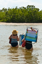 Back View, Long Distance Of Two Adult Woman In Bathing Suits And Straw Hats Wading Through Calm, Backwater Carrying Beach Chairs And Towels To An Isolated, Tropical, Island On The Gulf Of Mexico