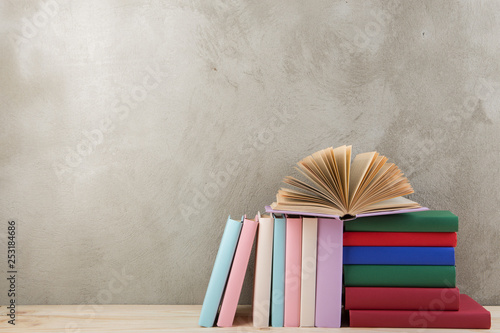 Photo sur Toile Amsterdam Education and reading concept - group of colorful books on the wooden table, concrete wall blackboard