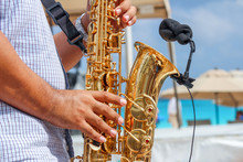Man Playing The Saxophone In The Beach