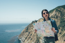 Lost Asian Woman Hiker With Backpack Checks Paper Map To Find Directions In Wilderness Area. Young Girl Hiking Trip In Beautiful Coastline In Big Sur California USA. Chinese Traveler In Sunglasses.
