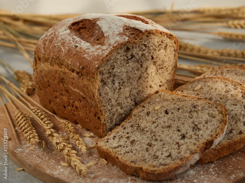 Fotografie, Obraz  sliced grain bread, on a wooden board with ears and grains