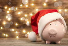 Piggy Bank With Santa Hat On Table Against Blurred Christmas Lights. Space For Text