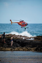 Helicopter Dropping Rescue Diver Off Hawaiian Beach.