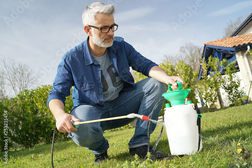 Man using garden sprayer on lawn in backyard