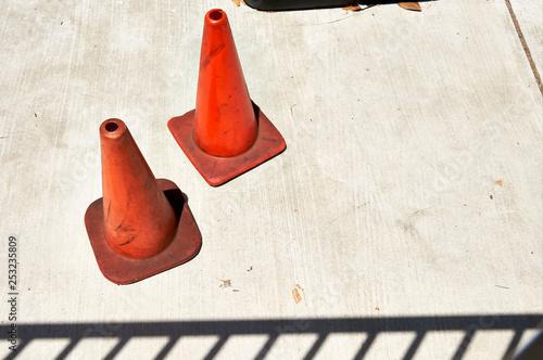 two orange traffic cones on concrete