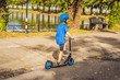 Boy riding scooters, outdoor in the park, summertime. Kids are happy playing outdoors