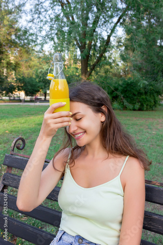 Young woman is tired of hot weather  Girl is holding a cold bottle