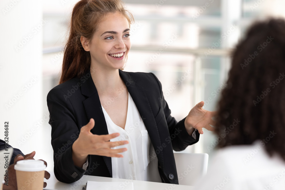 Fototapeta Young business woman talking with staff at formal meeting briefing