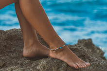 Suntanned Girl Legs With Boho Style Bracelet On Right One, Sits On Seacliff,