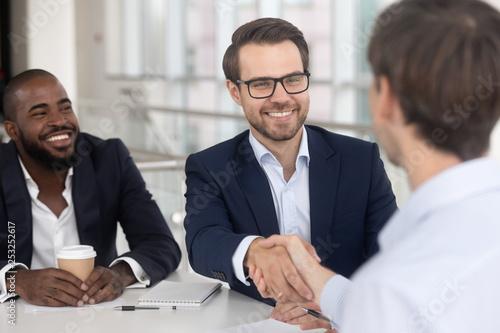 Fotografía  Positive diverse business partners shaking hands starting meeting