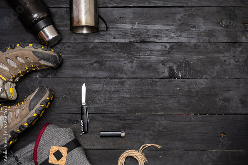 Obraz Preparing for a hiking trip: backpacking things and clothes flat lay. Top view of trekking boots, tourist rucksack and camping acessories on black background - fototapety do salonu