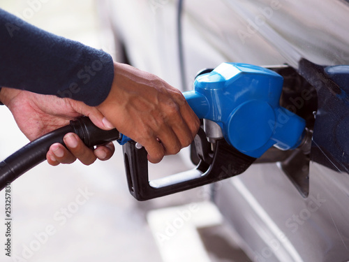 Tablou Canvas Closeup hand man pumping gasoline fuel in car at gas station.