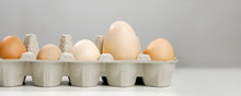 Close-up View Of Raw Chicken Eggs In Egg Box On Light Background