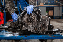 A Close-up Of A Young Man Repairman In A Working Uniform Of Cars Is Repairing An Automatic Gearbox Of A Used Car In An Auto Repair Shop. The Concept Of Car Repair And Car Repair Shop