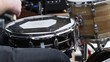 Close up on snare drum as the drummer plays during an outdoor show.