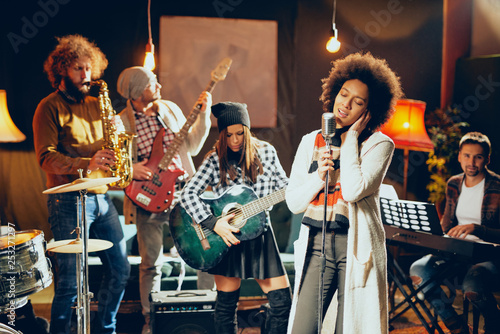 Mixed race woman singing. In background band playing instruments. Home studio interior. - 253271297