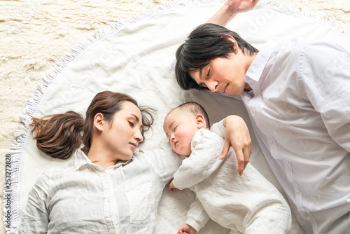 お昼寝する赤ちゃんと両親