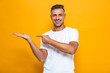 Happy excited man posing isolated over yellow wall background pointing.