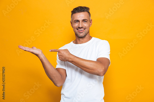 Fotografia  Happy excited man posing isolated over yellow wall background pointing