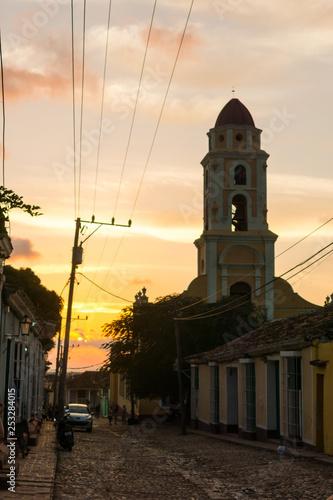 Fotografie, Tablou  Cuban street sunset with oldtimer in Trinidad, Cuba