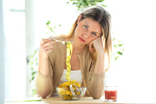 Worried Beautiful Woman Holding Fork With Measuring Tapes Sitting In Living Room At Home.
