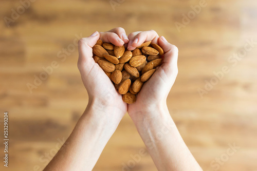 Photo Young woman hands forming heart shape holding almonds nuts at home