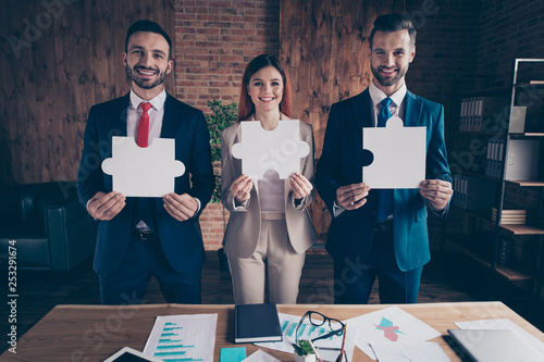 Portrait of three nice chic classy elegant stylish cheerful executive managers holding in hands showing big large puzzle in loft industrial interior workplace workstation