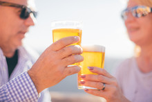 Retired Couple Drinking Beer In Sunny Day - Focus On Clinking Glasses