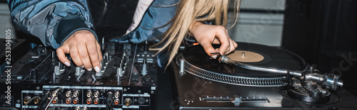 panoramic shot of dj woman standing near dj mixer and vinyl record - 253304805