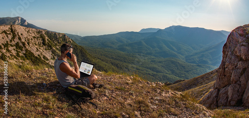 Foto  man freelancer with laptop, call by cellphone, on beauty mountains landscape